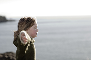 Profile of girl stand on cliff by oceanの写真素材 [FYI01992095]