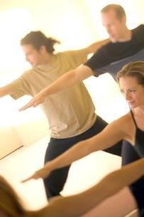 People practicing yoga, warrior poseの写真素材 [FYI01992196]