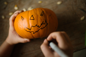 Child drawing face on pumpkin with a penの写真素材 [FYI01992223]