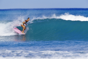 Female surfer riding a waveの写真素材 [FYI01992227]