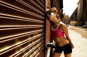 Woman runner resting against garage doorの写真素材 [FYI01992234]