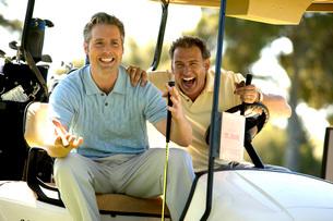 Men relaxing with cigars in golf cartの写真素材 [FYI01992295]