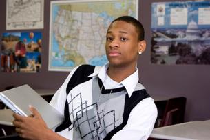 Teenage boy in classroom with laptopの写真素材 [FYI01992315]