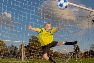 Boy goalie catching soccer ballの写真素材 [FYI01992326]