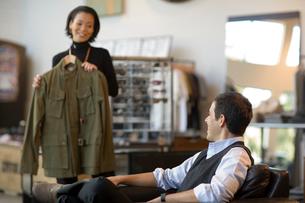 Sales clerk showing man jacket in storeの写真素材 [FYI01992338]