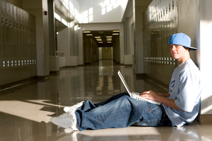 Boy in school hallway with laptopの写真素材 [FYI01992357]