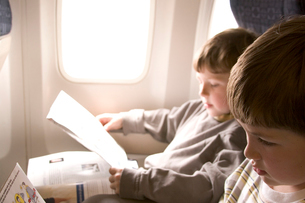 Boys reading safety pamphlets on a planeの写真素材 [FYI01992382]