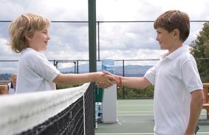Young shaking hands over tennis netの写真素材 [FYI01992399]