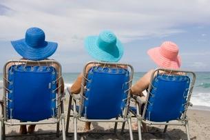 women wearing straw hats in beach chairsの写真素材 [FYI01992418]
