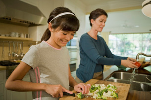 mother and daughter chopping vegetablesの写真素材 [FYI01992474]