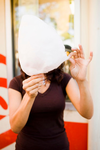 Woman eating cotton candyの写真素材 [FYI01992673]