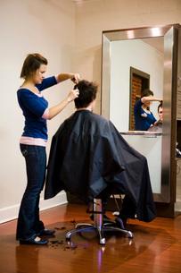 Female hairdresser cutting man's hairの写真素材 [FYI01992737]