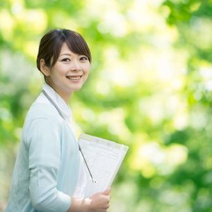 カルテを持ち微笑む看護師の写真素材 [FYI01992760]