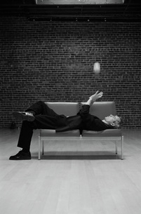 Man tossing ball while laying on chairの写真素材 [FYI01992787]