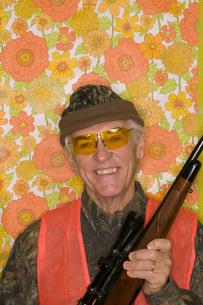 Man in hunting gear holding rifleの写真素材 [FYI01992830]