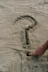 Man drawing question mark in sandの写真素材 [FYI01992857]