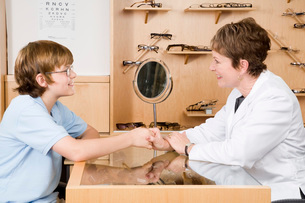 optician shaking hands with boyの写真素材 [FYI01992900]