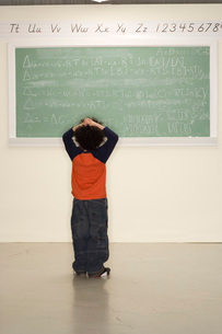 Child frustrated looking at blackboardの写真素材 [FYI01992929]