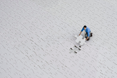 man putting together jigsaw puzzleの写真素材 [FYI01992940]