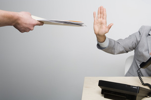 Businessman holding hand up to paperworkの写真素材 [FYI01992986]