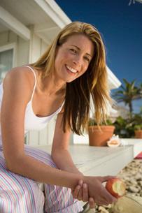Woman smiling eating appleの写真素材 [FYI01993016]