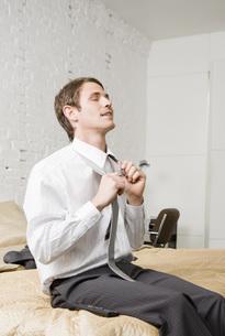 Businessman untying necktieの写真素材 [FYI01993028]