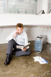 man sitting on floor next to computerの写真素材 [FYI01993040]