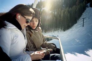 Teenagers using mp3 players on ski liftの写真素材 [FYI01993043]