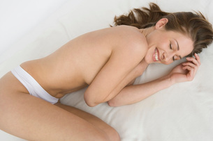 Nude woman laying on bedの写真素材 [FYI01993088]