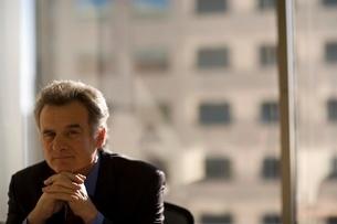 Mature businessman resting head on handsの写真素材 [FYI01993150]