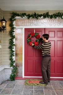 Man hanging Christmas wreathの写真素材 [FYI01993180]
