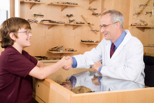 Male optician shaking hands with boyの写真素材 [FYI01993354]