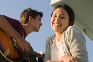 Teenage couple standing on lifeguard hutの写真素材 [FYI01993358]