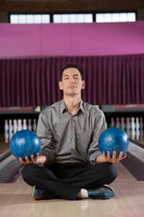 Man meditating with bowling ballsの写真素材 [FYI01993361]