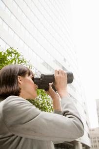 woman looking through binocularsの写真素材 [FYI01993401]