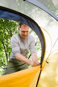 Man zipping up tentの写真素材 [FYI01993406]