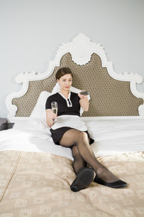 Maid drinking champagne in bedの写真素材 [FYI01993411]
