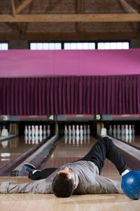 Man laying with bowling ballの写真素材 [FYI01993431]