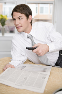 Businessman pointing remote controlの写真素材 [FYI01993480]