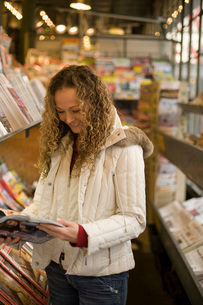 woman reading magazine in news standの写真素材 [FYI01993560]