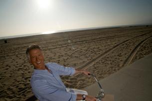 Man riding bicycle on beachの写真素材 [FYI01993571]