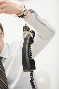 man handcuffed to telephone receiverの写真素材 [FYI01993625]