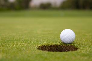 Golf ball rolling towards holeの写真素材 [FYI01993687]