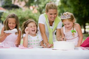 Mother serving daughters birthday cakeの写真素材 [FYI01993700]