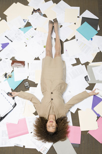woman laying on pile of paperworkの写真素材 [FYI01993836]