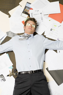 Businessman laying on pile of paperworkの写真素材 [FYI01993843]