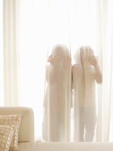 Children hiding behind sheer curtainsの写真素材 [FYI01993845]