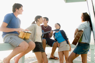 Teenagers playing music at beach houseの写真素材 [FYI01993914]
