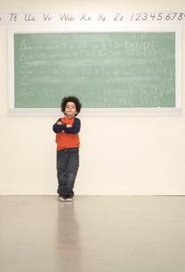 Boy standing in front of blackboardの写真素材 [FYI01993925]