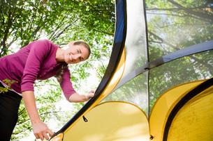 Woman zipping up tentの写真素材 [FYI01994035]
